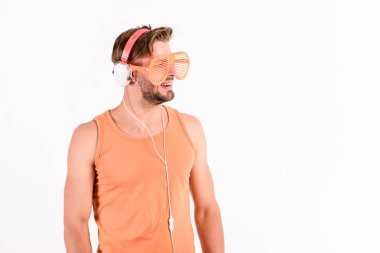 Technology and entertainment. Modern life. Handsome man with headphones and sunglasses. Party concept. Summer music chart. Guy unshaven face listening summer music. Dj boy. Popular summer track list