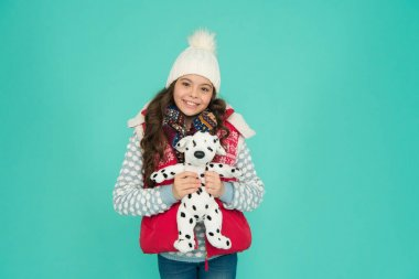 Happy holiday. winter activity and fun. childhood happiness. fashion kid turquoise background. child happy to play with toy. kid toy shop. small girl hold dog toy. kid love her fluffy pet puppy