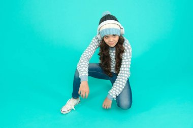 cool kid turquoise background. music for winter playlist. favorite winter song. girl enjoy favorite tune. music mood. small child knitted sweater and hat. She is listening to music on headphones