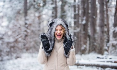 Girl in mittens and fur hat. funny and happy woman. best holiday ever. girl wear warm clothing. Enjoying nature wintertime. Portrait of excited woman in winter wood. white snow tree