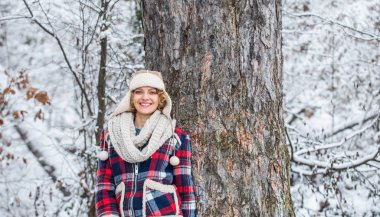 woman smiling near tree. holiday winter day. pretty woman in warm clothing. Enjoying nature wintertime. Portrait of excited woman in winter. Cheerful girl outdoor relax. woman checkered jacket