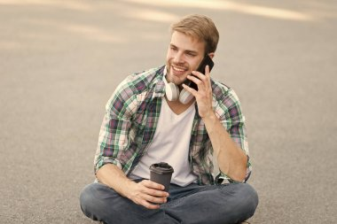 Call friend. Wellbeing and health. Having coffee break. Man sit on ground while drinking coffee. Relax and recharge. Have fun during break. Guy carefree student enjoy coffee outdoors. Life balance