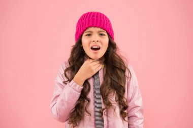 Sore throat. Cold climate weather. Little girl sick ill pink background. Kid puffer jacket and knitted hat. Winter cold flu. Health care. Feeling bad. Medical treatment. Flu remedies. Flu season