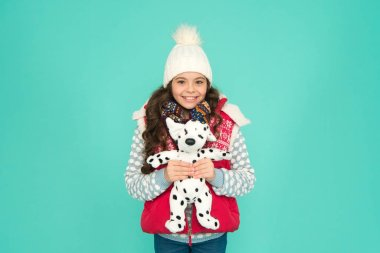 Winter time fun. child happy to play with toy. kid toy shop. small girl hold dog toy. kid love her fluffy pet puppy. winter activity and fun. childhood happiness. fashion kid turquoise background