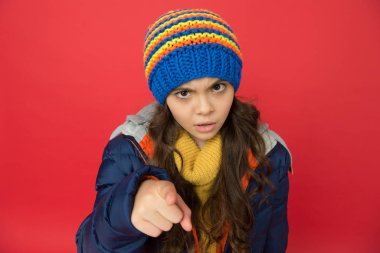 small beauty red background. little girl puffer jacket and knitted hat. care yourself in cold weather. kid pointing finger. angry child in warm winter clothes. seasonal fashion for kids