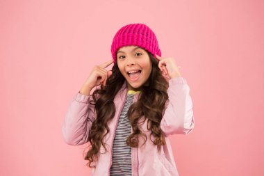 Active rest. winter holiday activity. little beauty pink background. kid fashion style. child knitted hat and puffer coat. happy small girl. no flu this winter. wear warm clothes in cold season