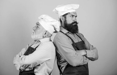 chef battle. who is the best. family dinner. father and son cooking together. commercial kitchen at restaurant. professional chefs. serious men in cook hat. mature bearded chef