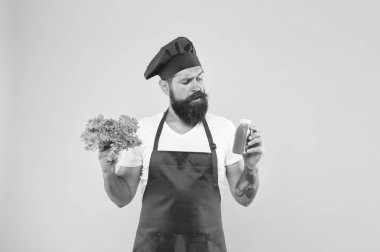 hipster decide what to choose. healthy eating and dieting concept. cook hold fresh salad and smoothie in bottle. organic eco vegan products. bearded man chef in apron and hat. cooking healthy food