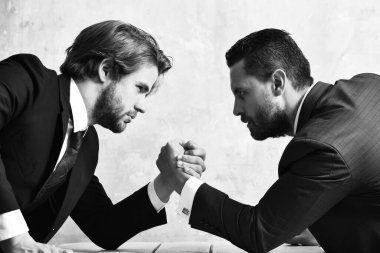 Conflict. Businessmen arm wrestling in suit in office.