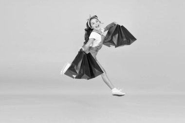 Inspiring shopping. Trends and brands. Towards discounts. Happy girl jump with shopping bags. Little child smile with paper bags. Holidays preparation and celebration. Shopping on black friday