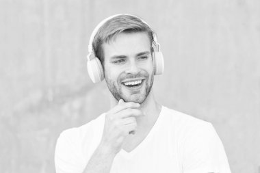 Noise Reduction. Wireless Earpiece. Handsome guy wear headphones grey background. Man listen modern music. Modern technology. Modern and contemporary music. Hobby leisure. Foldable Stereo Headphones