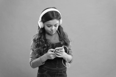 answer the email. small child make play list on smartphone. small girl use mp3 player. study in modern life. girl use digital device. casual fashion for kids. kid long hair listen music in headset