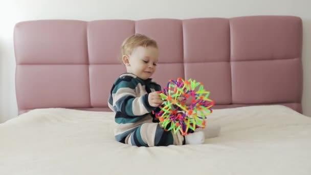 Portrét jednoletého chlapečka, který si hraje s barevnou plastovou hračkou sedící na posteli. Batole, užívej si ranní učení. Vývojové hračky