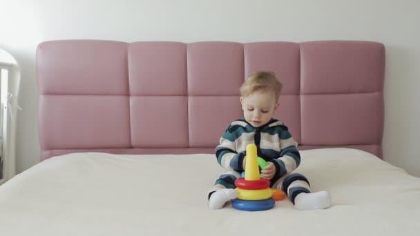 Netter Junge, der mit Lernspielzeug spielt. Bunte Kunststoffringtürme für Kinder. Einjähriger Junge spielt mit buntem Plastikspielzeug auf dem Bett