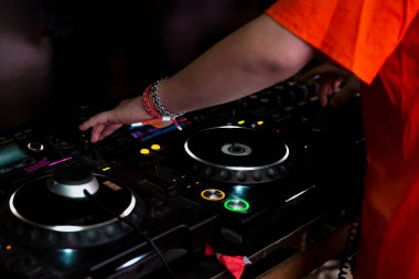 close up of dj playing on mixer lighting at club