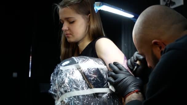 tatuatore nellopera. Artigiano professionista fa libellula tatuaggio per donna o ragazza in laboratorio.
