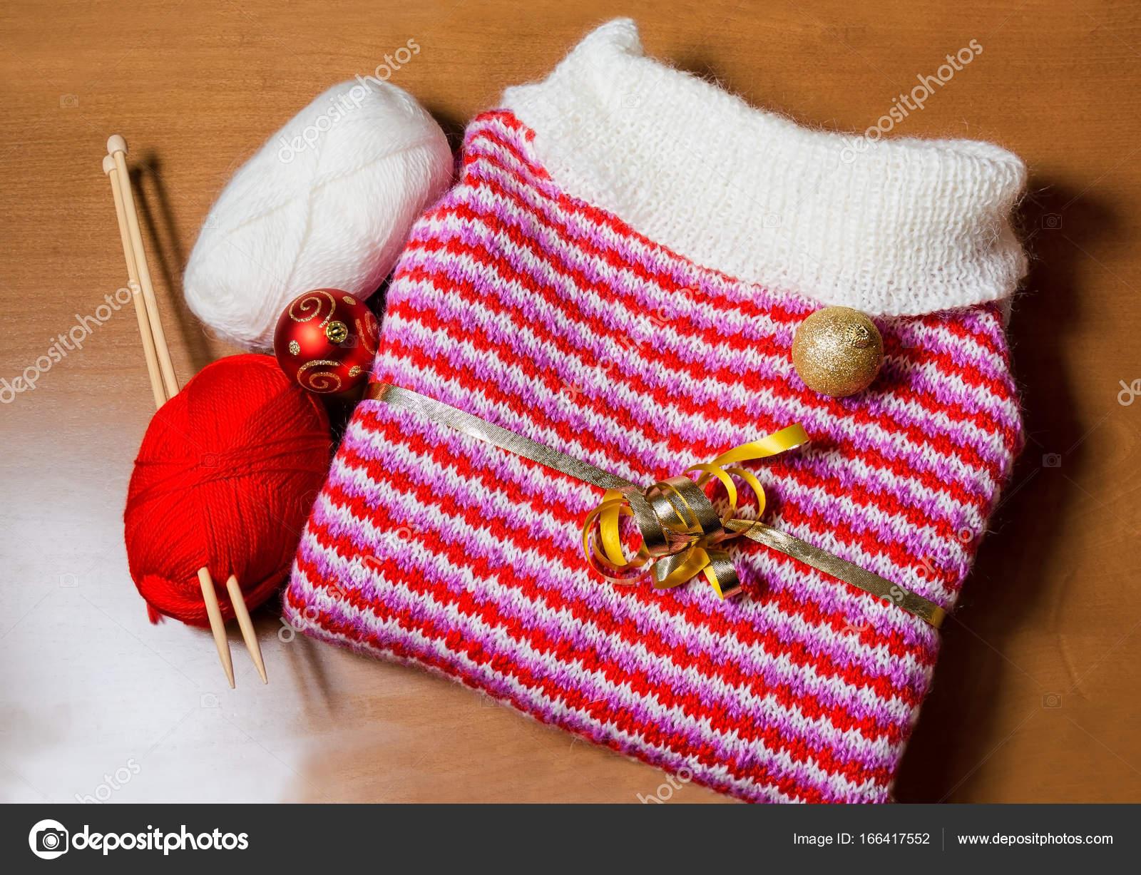 c5f45134dca Teplé červené a bílé pletený svetr a vánoční koule na dřevěné pozadí —  Stock fotografie