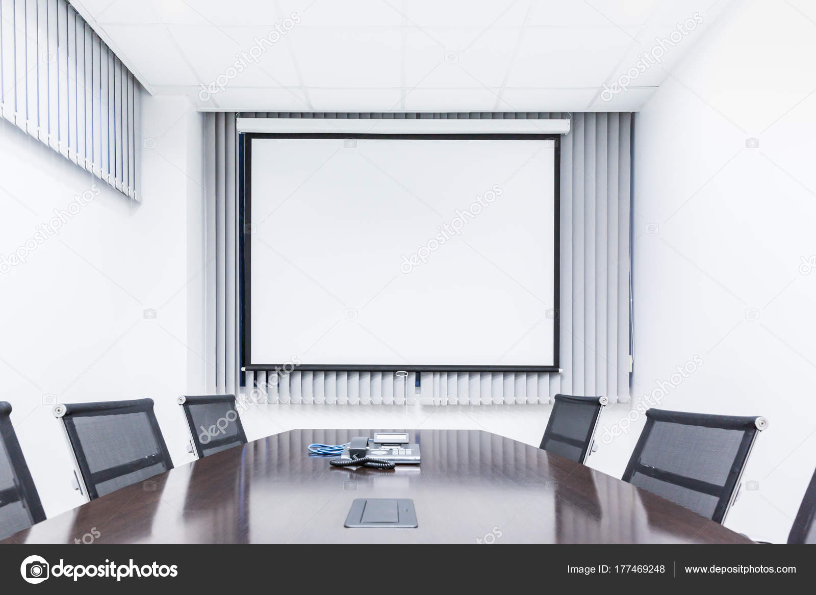 Meeting room with table chair and projector screen in modern off ...