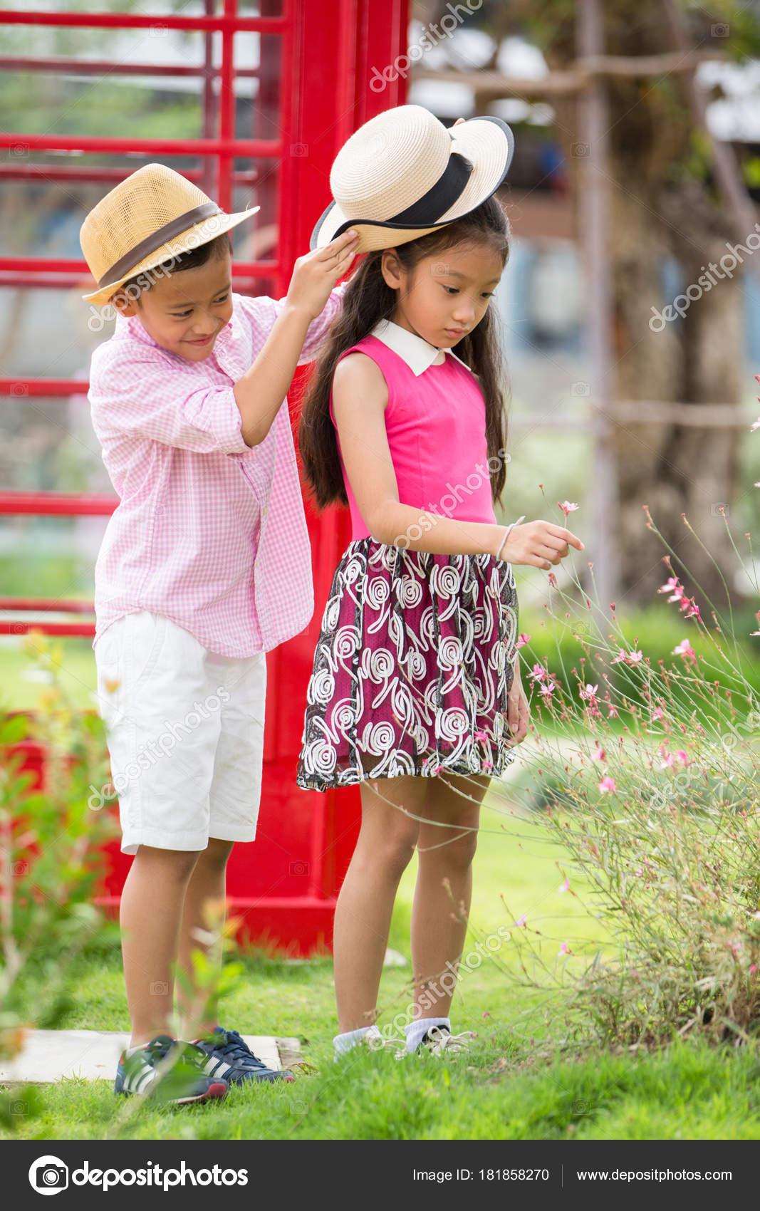 Poco Asia Chico y chica disfrutan jugando en el jardín, San Valentín ...