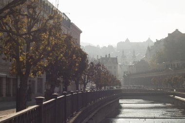 Karlovy Vary Nov.11.2019. Misty misty morning over the Tepla River and on the shore. To the right is the Mill Colonnade with the tower of Saint Mary Magdalena Church in the background.