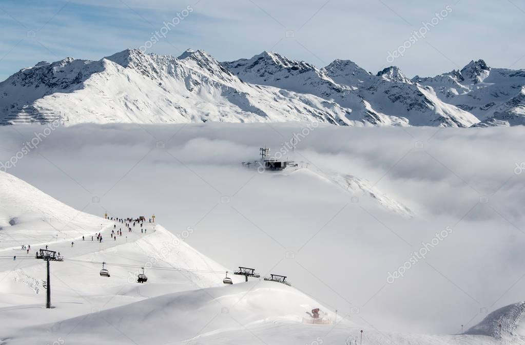 Ski lift on the top of the mountain in St. Anton am Arlberg, Austria, above the clouds