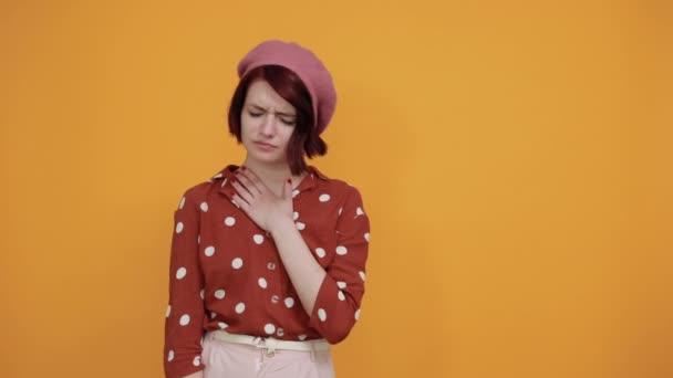 attraktive Frau mit müdem und krankem Gesichtsausdruck auf isoliertem gelben Hintergrund