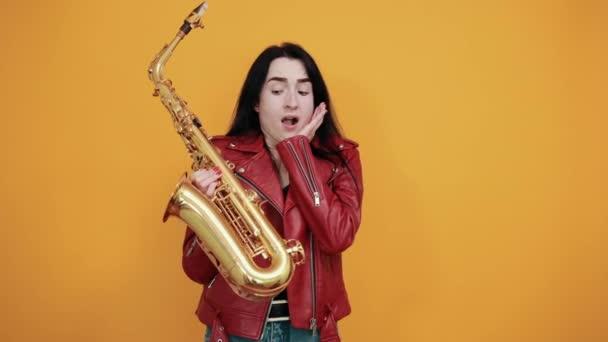 Megdöbbent fiatal nő tartja a száját nyitott és szaxofon, kezét az arcára