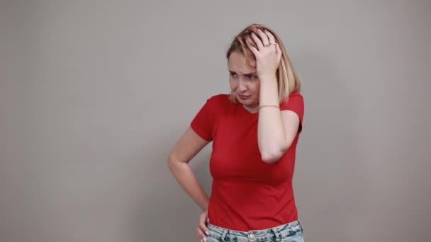 Hezká mladá žena se dívá stranou, dává ruku na hlavu izolované na šedé zdi