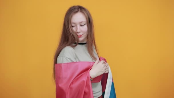 Young girl showing thumb aside, wearing casual clothes covered bisexual flag