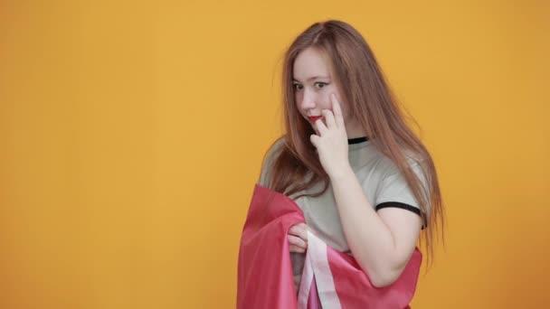 Mladá žena v neformálních šatech drží ruce stranou, přikryté bisexuální vlajkou