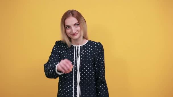 Usmívající se mladá žena dívá přímo, dělá v pořádku gesto