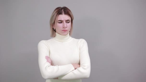Portrait of confused young woman looking aside and covering chin with hand