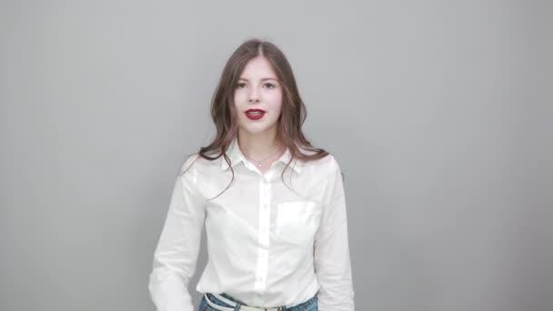 Vonzó nő fehér ingben mutatja három ujját a kamera előtt, boldognak látszik.