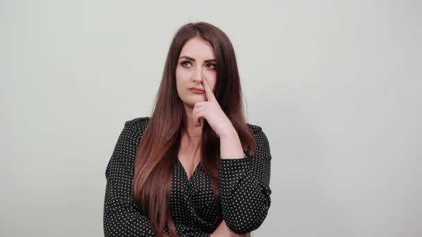 Elbűvölő kaukázusi nő, az állán tartja az ujját, félrenéz..