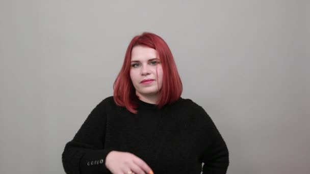 redhead fat lady in black sweater seductive woman touches index finger to lip