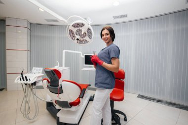 The dentist is standing near the dental chair