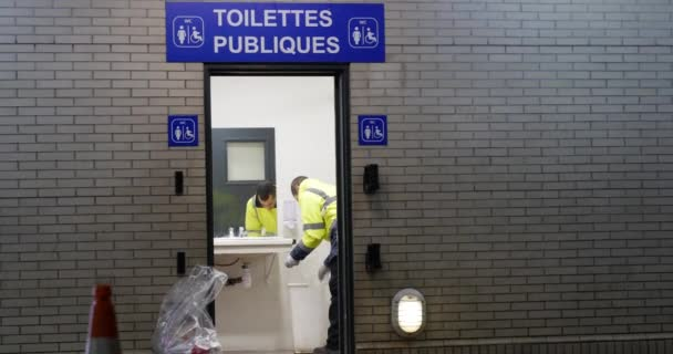 Close shot of Arabian man cleaning toilets in Paris bus station with yellow vest, France, 5.2.2020