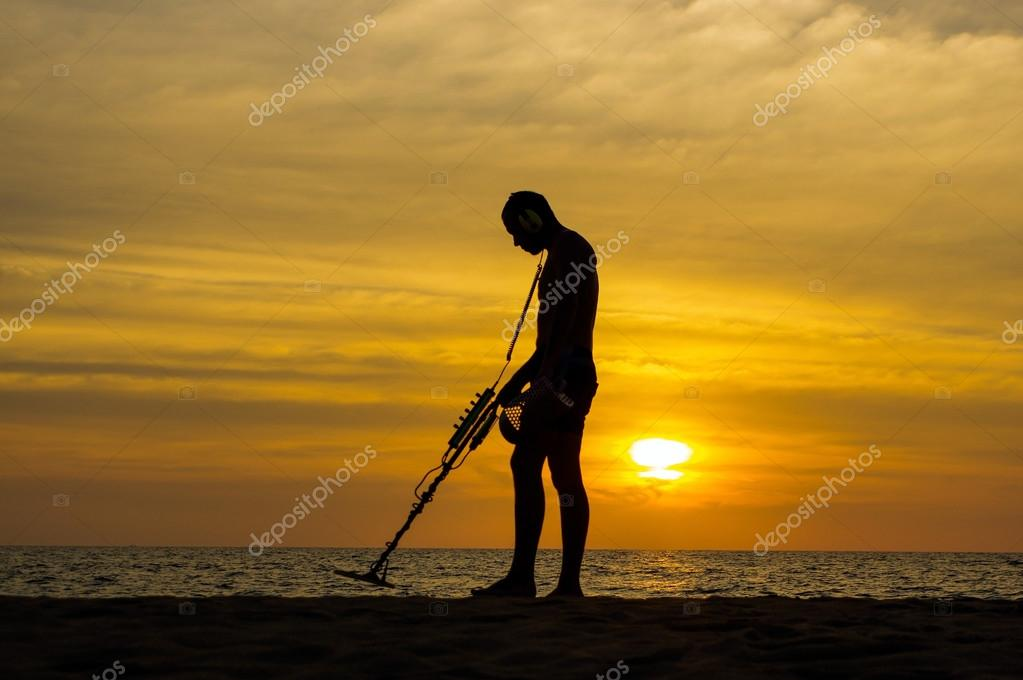 Treasure hunter with Metal detector on sunset the beach