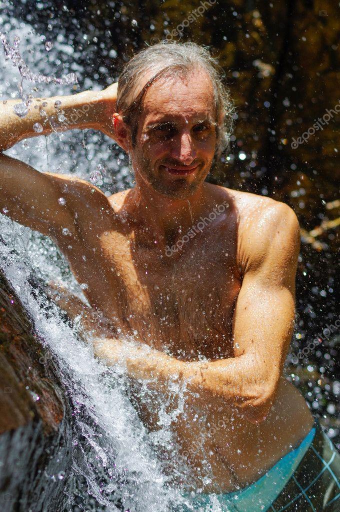 Man taking a relaxing shower under waterfall. outside