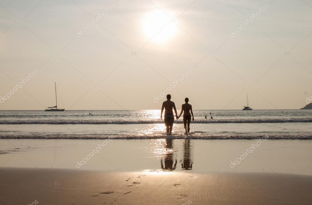 silueta de pareja caminando en la playa al atardecer cogidos de la ...