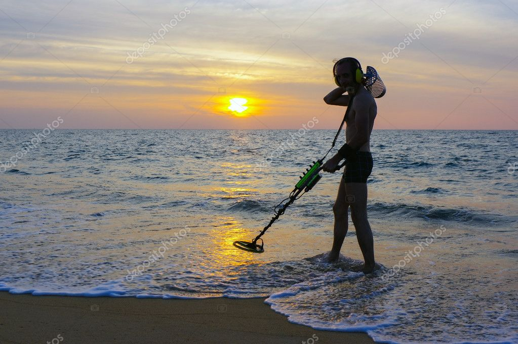 Treasure hunter with Metal detector on the sunset the beach