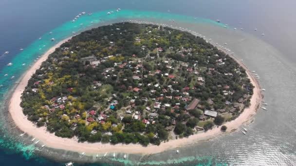 Kis kerek trópusi sziget resort hotel fehér homok, pálmafák és türkiz óceán vagy tenger.