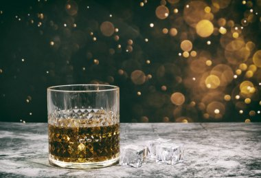 Whiskey and ice on a golden bokeh background for Happy Day.