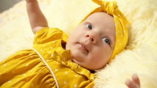 Portrét. Dítě ve žlutých šatech a žlutém obvazu na hlavě, baví se s úsměvem a gestem.