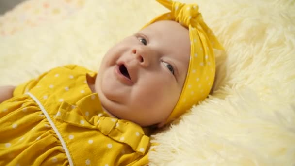 Portrét. Dítě ve žlutých šatech a žlutém obvazu na hlavě, kýchne.