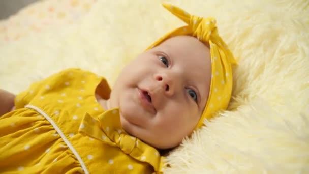 Portrét. Dítě ve žlutých šatech a žlutém obvazu na hlavě, zívá