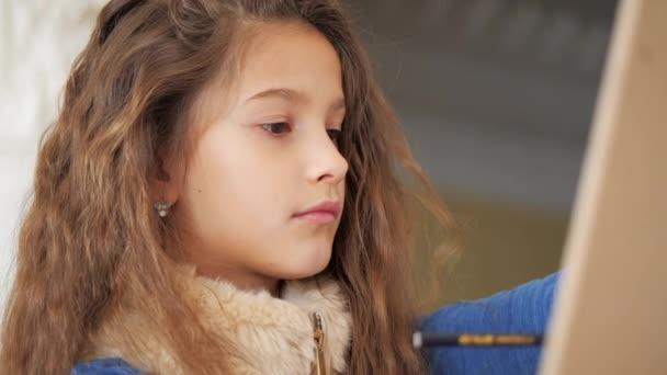 Portrét. Mladá dívka s kudrnatými blond vlasy kreslí tužkou na stojanu.