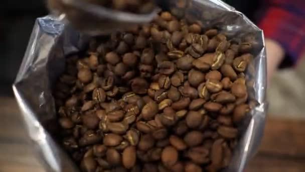Barista získává kávová zrna lžící z balíčku