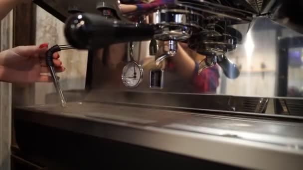 Barista produkuje páru z automatu na kávu