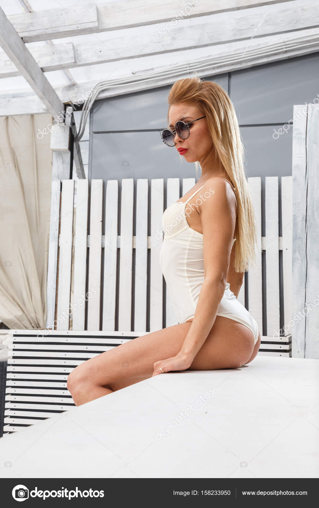 6a6285543b Beautiful blonde woman posing sensually on white fence background — Photo  by ...